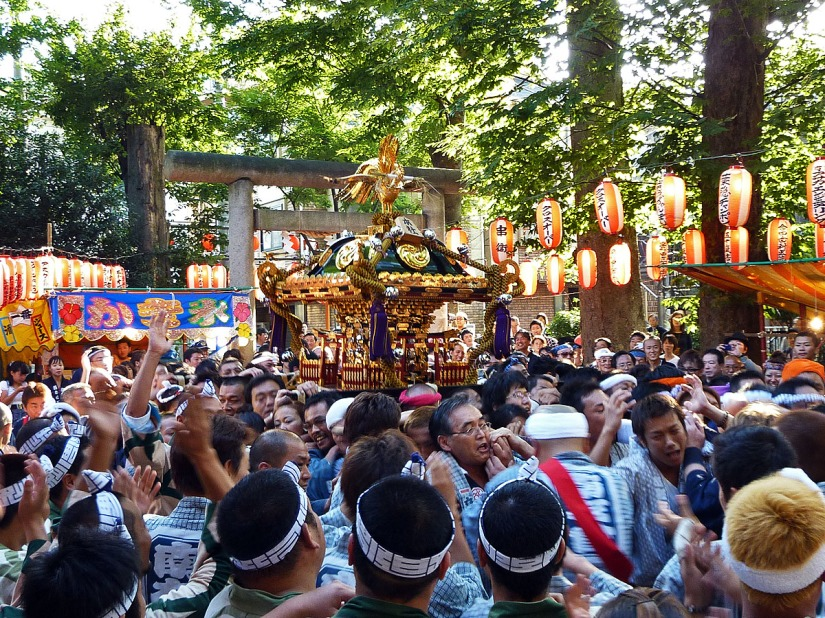 Carrying a mikoshi. Image credit.